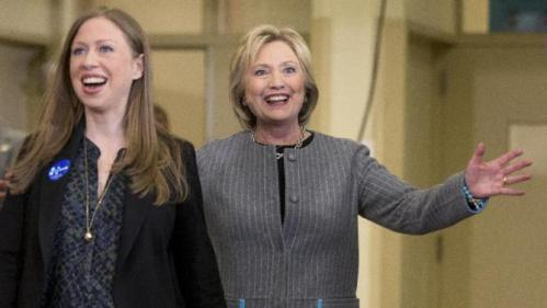 Democratic presidential candidate Hillary Clinton, accompanied by her daughter Chelsea Clinton, reacts to applause as she arrives for a rally at Abraham Lincoln High School in Council Bluffs, Iowa, Sunday, Jan. 31, 2016. (AP Photo/Andrew Harnik)