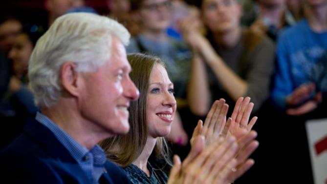 Former President Bill Clinton, left, and his daughter Chelsea Clinton, right, applauds as Democratic presidential candidate Hillary Clinton speaks at a rally at Abraham Lincoln High School in Des Moines, Iowa, Sunday, Jan. 31, 2016. (AP Photo/Andrew Harnik)
