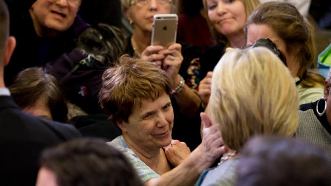A woman in the audience touches the cheek of Democratic presidential candidate Hillary Clinton at a rally at Abraham Lincoln High School in Des Moines, Iowa, Sunday, Jan. 31, 2016. (AP Photo/Andrew Harnik)