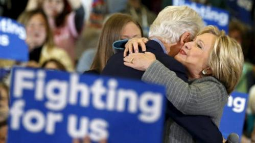 U.S. Democratic presidential candidate Hillary Clinton embraces former U.S. President Bill Clinton as daughter Chelsea Clinton looks on during a campaign rally at Abraham Lincoln High School in Des Moines, Iowa January 31, 2016. REUTERS/Adrees Latif