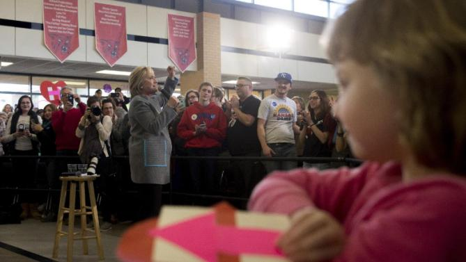 Magnolia Mandelko, 5, holds a campaign card as Democratic presidential candidate Hillary Clinton, left, speaks at a rally at Abraham Lincoln High School in Council Bluffs, Iowa, Sunday, Jan. 31, 2016. (AP Photo/Andrew Harnik)