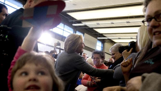 Magnolia Mandelko, 5, left, holds a campaign card as Democratic presidential candidate Hillary Clinton, center, greets members of the audience at a rally at Abraham Lincoln High School in Council Bluffs, Iowa, Sunday, Jan. 31, 2016. (AP Photo/Andrew Harnik)
