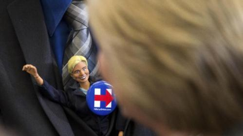 A man tucks a doll, left, of Democratic presidential candidate Hillary Clinton into his suit jacket as Clinton, right, greets members of the audience at a rally at Abraham Lincoln High School in Council Bluffs, Iowa, Sunday, Jan. 31, 2016. (AP Photo/Andrew Harnik)
