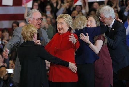 Democratic U.S. presidential candidate Hillary Clinton celebrates with former U.S. Senator Tom Harkin (L), her daughter Chelsea (2ndR) and her husband, former President Bill Clinton (R), at her caucus night rally in Des Moines, Iowa February 1, 2016. REUTERS/Brian Snyder