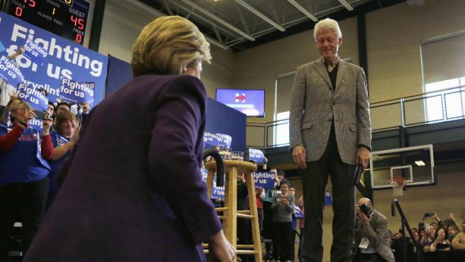 Former President Bill Clinton watches as his wife, Democratic presidential candidate Hillary Clinton takes the stage after introducing her at a campaign event, Tuesday, Feb. 2, 2016, in Nashua, N.H. (AP Photo/Elise Amendola)