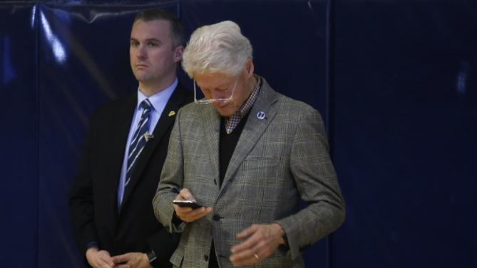 Former President Bill Clinton checks his phone backstage as Democratic presidential candidate Hillary Clinton finishes her remarks at a campaign event, Tuesday, Feb. 2, 2016, in Nashua, N.H. (AP Photo/Elise Amendola)