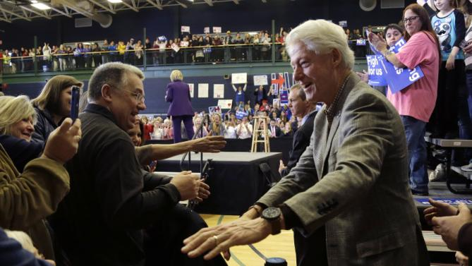 Former President Bill Clinton greets potential voters as Democratic presidential candidate Hillary Clinton (center, back) finishes her remarks at a campaign event, Tuesday, Feb. 2, 2016, in Nashua, N.H. (AP Photo/Elise Amendola)