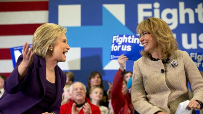 Democratic presidential candidate Hillary Clinton turns toward former Arizona Rep. Gabby Giffords, right, at a Clinton event in Hampton, N.H., Tuesday Feb. 2, 2016, Clinton's first day in New Hampshire after winning the Iowa Caucus. (AP Photo/Jacquelyn Martin)