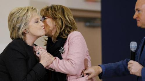 Democratic presidential candidate Hillary Clinton embraces former Arizona Rep. Gabrielle Giffords, center, and her husband astronaut Mark Kelly during a campaign stop, Wednesday, Feb. 3, 2016, in Derry, N.H. (AP Photo/Matt Rourke)