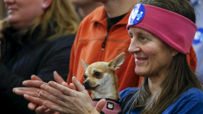 Martha Muehe of Merrimac, Massachusetts holds her dog Gracie, a chihuahua, as she applauds U.S. Democratic presidential candidate Hillary Clinton during a campaign rally at the Derry Boys and Girls Club in Derry, New Hampshire February 3, 2016. REUTERS/Adrees Latif