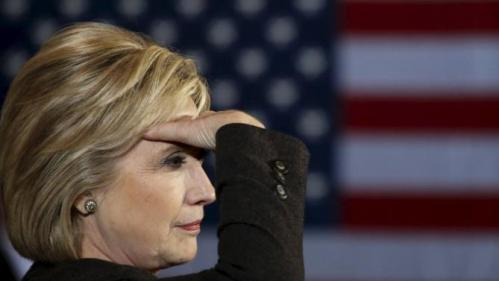 U.S. Democratic presidential candidate Hillary Clinton blocks her eyes from light while taking questions from the crowd during a campaign event in Dover, New Hampshire February 3, 2016. REUTERS/Adrees Latif