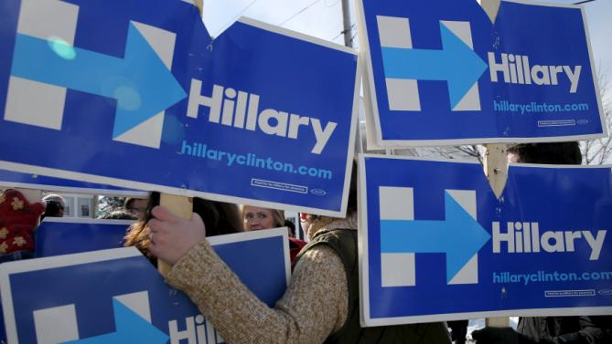 U.S. Democratic presidential candidate Hillary Clinton greets campaign volunteers holding signs while going to door-to-door to greet voters in a neighborhood in Manchester, New Hampshire February 6, 2016.  REUTERS/Brian Snyder      TPX IMAGES OF THE DAY