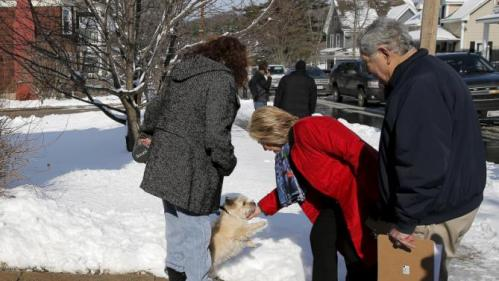 U.S. Democratic presidential candidate Hillary Clinton pets a dog while going to door-to-door to greet voters in a neighborhood in Manchester, New Hampshire February 6, 2016. REUTERS/Brian Snyder