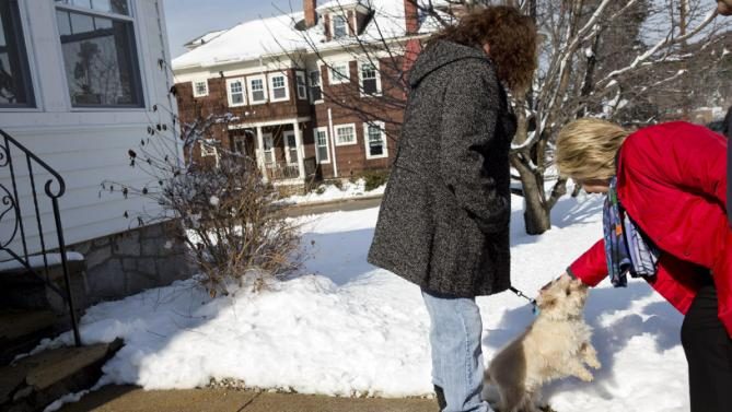 Democratic presidential candidate Hillary Clinton pets a local dog during a campaign stop in a neighborhood in Manchester, N.H., Saturday Feb. 6, 2016. (AP Photo/Jacquelyn Martin