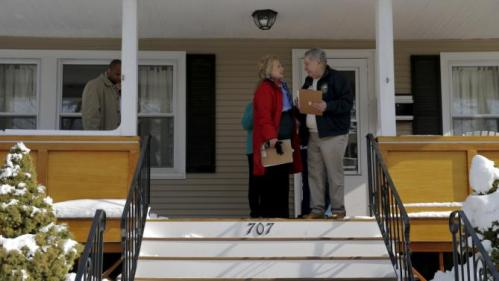 U.S. Democratic presidential candidate Hillary Clinton talks to New Hampshire State Senator Lou D'Allesandro on a porch while going to door-to-door to greet voters in a neighborhood in Manchester, New Hampshire February 6, 2016. REUTERS/Brian Snyder
