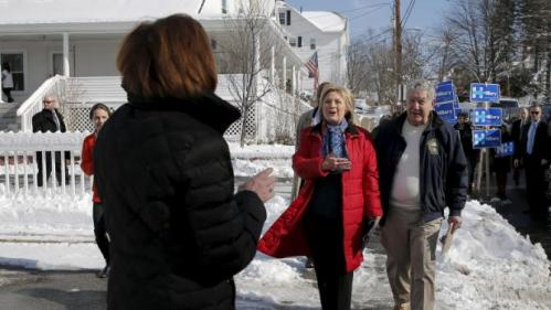 U.S. Democratic presidential candidate Hillary Clinton is greeted by a local resident (L) while canvassing door-to-door to greet voters in a neighborhood in Manchester, New Hampshire February 6, 2016. REUTERS/Brian Snyder