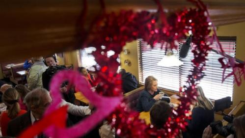 Seen through Valentine's Day heart decorations, Democratic presidential candidate Hillary Clinton campaigns at the Belmont Hall & Restaurant in Manchester, N.H., Saturday Feb. 6, 2016. (AP Photo/Jacquelyn Martin)