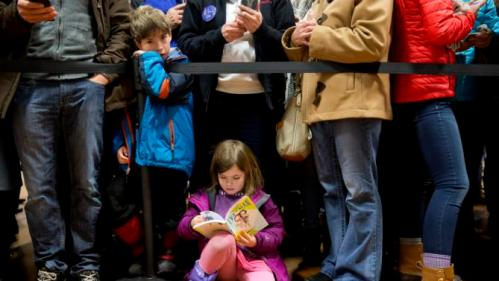 "Audrey Clendenning, 6, of Concord, N.H., reads as she and others wait for Democratic presidential candidate Hillary Clinton to arrive in the overflow room of a ""Get Out the Vote"" event at Rundlett Middle School, in Concord, N.H., Saturday Feb. 6, 2016. (AP Photo/Jacquelyn Martin)"