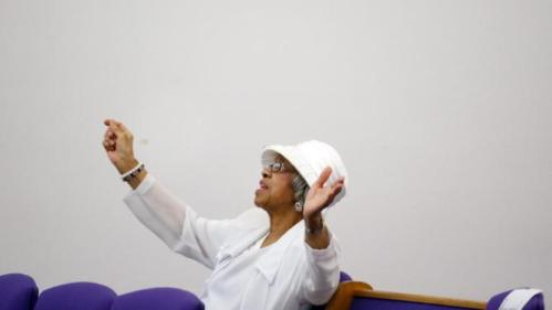 An audience member prays before an appearance by Democratic presidential candidate Hillary Clinton at the House Of Prayer Missionary Baptist Church, Sunday, Feb. 7, 2016 in Flint, Mich. (AP Photo/Paul Sancya)
