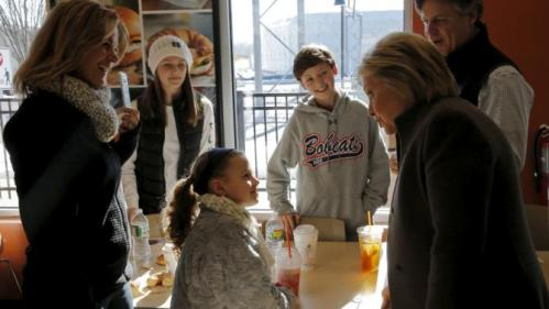 U.S. Democratic presidential candidate Hillary Clinton talks with a family during a stop at a Dunkin' Donuts in Manchester, New Hampshire February 7, 2016. REUTERS/Brian Snyder