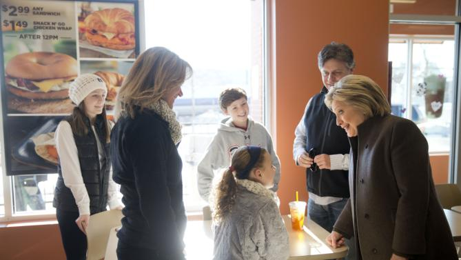 Democratic presidential candidate Hillary Clinton, right, meets a family, Sunday, Feb. 7, 2016, at a Dunkin' Donuts in Manchester, N.H. (AP Photo/Matt Rourke)