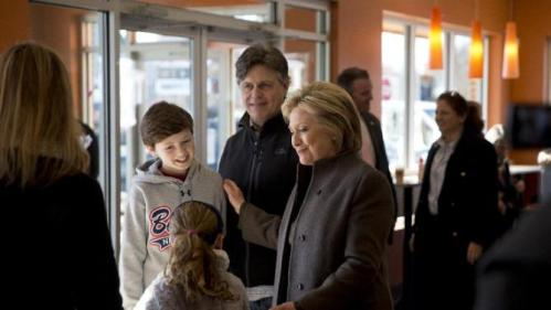 Democratic presidential candidate Hillary Clinton meets a family, Sunday, Feb. 7, 2016, at a Dunkin' Donuts in Manchester, N.H. (AP Photo/Matt Rourke)