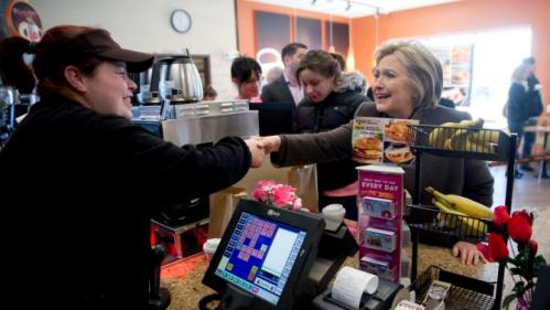 Democratic presidential candidate Hillary Clinton shakes hands with a cashier, Sunday, Feb. 7, 2016, at a Dunkin' Donuts in Manchester, N.H. (AP Photo/Matt Rourke)