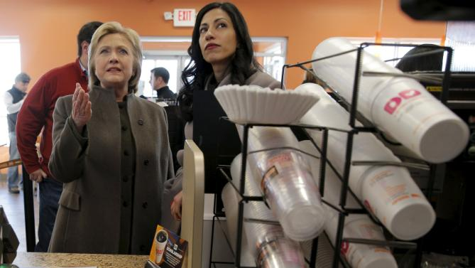 U.S. Democratic presidential candidate Hillary Clinton and her aide Huma Abedin (R) look at the menu during a stop at a Dunkin' Donuts in Manchester, New Hampshire February 7, 2016.  REUTERS/Brian Snyder