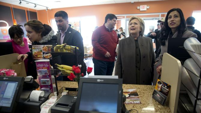 Democratic presidential candidate Hillary Clinton, accompanied by her aide Huma Abedin, right, looks to place an order Sunday, Feb. 7, 2016, at a Dunkin' Donuts in Manchester, N.H. (AP Photo/Matt Rourke)