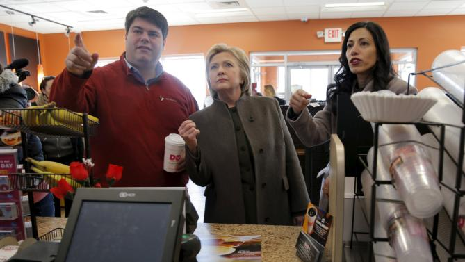 U.S. Democratic presidential candidate Hillary Clinton, New Hampshire State Director Mike Vlacich (L) and aide Huma Abedin (R) look at the menu during a stop at a Dunkin' Donuts in Manchester, New Hampshire February 7, 2016.  REUTERS/Brian Snyder