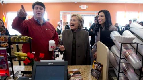 Democratic presidential candidate Hillary Clinton, center, accompanied by Mike Vlacich, New Hampshire state director, Hillary for America, and her aide Huma Abedin look to place their order Sunday, Feb. 7, 2016, at a Dunkin' Donuts in Manchester, N.H. (AP Photo/Matt Rourke)