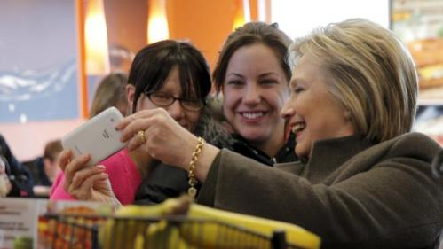 U.S. Democratic presidential candidate Hillary Clinton poses for a selfie during a stop at a Dunkin' Donuts in Manchester, New Hampshire February 7, 2016. REUTERS/Brian Snyder