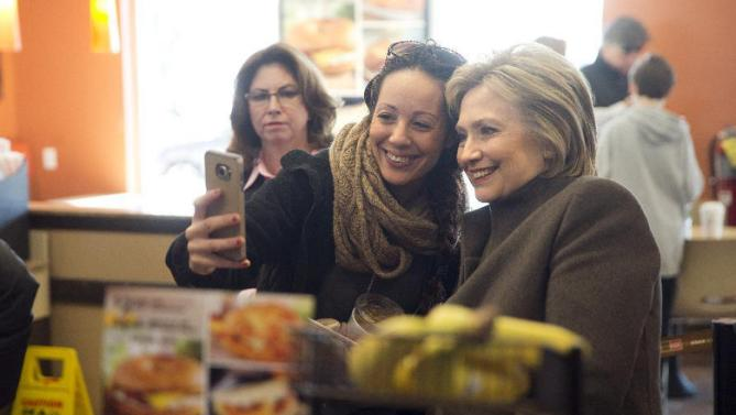 Democratic presidential candidate Hillary Clinton makes a selfie with a customer Sunday, Feb. 7, 2016, at a Dunkin' Donuts in Manchester, N.H. (AP Photo/Matt Rourke)