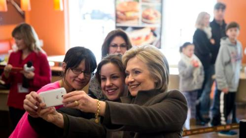 Democratic presidential candidate Hillary Clinton makes a selfie with customers, Sunday, Feb. 7, 2016, at a Dunkin' Donuts in Manchester, N.H. (AP Photo/Matt Rourke)