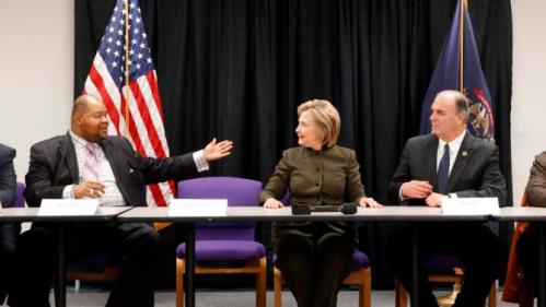 Kerry Nelson, left, Flint City Council President, motions to Democratic presidential candidate Hillary Clinton as Rep. Dan Kildee, D-Mich., listens during a meeting with officials at the House Of Prayer Missionary Baptist Church, Sunday, Feb. 7, 2016 in Flint, Mich. (AP Photo/Paul Sancya)