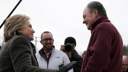 U.S. Democratic presidential candidate Hillary Clinton greets Frank Fiorina, the husband of U.S. Republican presidential candidate Carly Fiorina, outside a polling place in Derry, New Hampshire February 9, 2016, the day of New Hampshire's first-in-the-nation primary. REUTERS/Brian Snyder