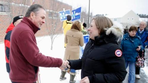 Frank Fiorina, husband of Republican presidential candidate Carly Fiorina shake hands with Chelsea Clinton, daughter of Democratic presidential candidate Hillary Clinton, as they campaign outside a polling place during the first-in-the-nation presidential primary, Tuesday, Feb. 9, 2016, in Derry, N.H. (AP Photo/Matt Rourke)