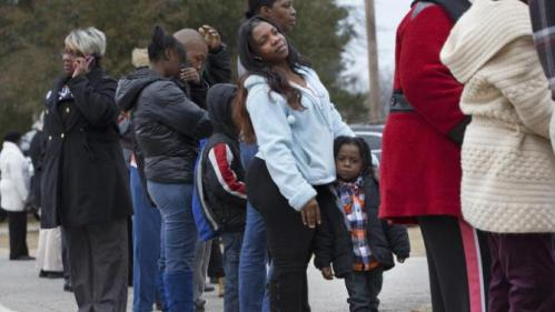 Angelan Wise, center, of Denmark, S.C., waits in line with her grandson Char-Vonhdre Williams, 3, to see Democratic presidential candidate Hillary Clinton speak at a town hall meeting at Denmark Olar Elementary School in Denmark, S.C., Friday Feb. 12, 2016. (AP Photo/Jacquelyn Martin)