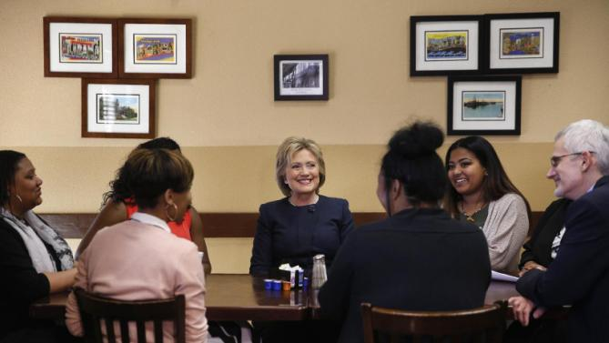 Democratic presidential candidate Hillary Clinton sits at a table with people at the Gritz Cafe, Saturday, Feb. 13, 2016, in Las Vegas. (AP Photo/John Locher)