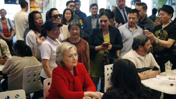 Democratic presidential candidate Hillary Clinton, in red, speaks with Nevada Assemblywoman Irene Bustamante Adams, bottom right, at Lee's Sandwiches during a campaign stop Sunday, Feb. 14, 2016, in Las Vegas. (AP Photo/John Locher)