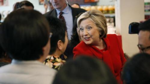 Democratic presidential candidate Hillary Clinton, in red, visits Lee's Sandwiches during a campaign stop Sunday, Feb. 14, 2016, in Las Vegas. (AP Photo/John Locher)