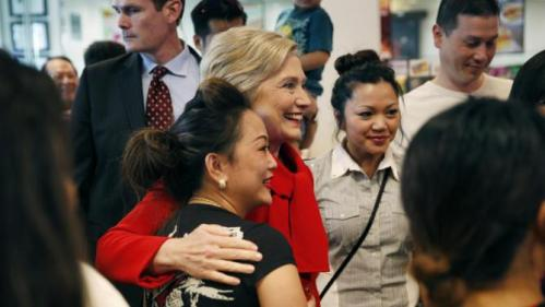 Democratic presidential candidate Hillary Clinton, center in red, visits Lee's Sandwiches during a campaign stop Sunday, Feb. 14, 2016, in Las Vegas. (AP Photo/John Locher)