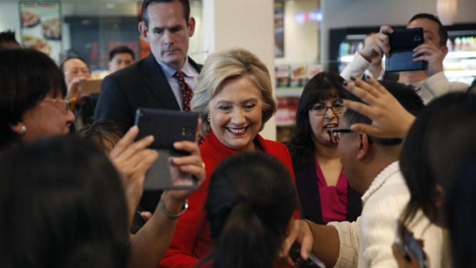 Democratic presidential candidate Hillary Clinton, center in red, meets with people at Lee's Sandwiches during a campaign stop Sunday, Feb. 14, 2016, in Las Vegas. (AP Photo/John Locher)