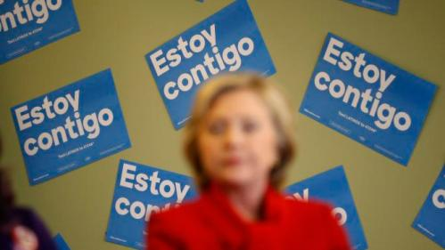 "Signs in Spanish that reads, ""I am with you,"" hang on a wall behind Democratic presidential candidate Hillary Clinton as she speaks at an event to meet with young immigrants, or so-called ""dreamers,"" and their families at a campaign office Sunday, Feb. 14, 2016, in Las Vegas. (AP Photo/John Locher)"