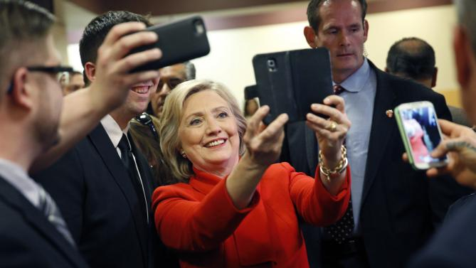 Democratic presidential candidate Hillary Clinton takes a selfie with an employee of Caesars Palace during a visit to the casino Sunday, Feb. 14, 2016, in Las Vegas. (AP Photo/John Locher)