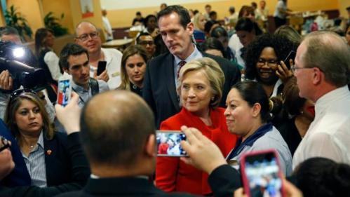 Democratic presidential candidate Hillary Clinton poses for pictures with employees of Caesars Palace during a visit to the casino Sunday, Feb. 14, 2016, in Las Vegas. (AP Photo/John Locher)