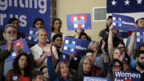 Supporters wave signs as Democratic presidential candidate Hillary Clinton speaks at a rally at Truckee Meadows Community College on Monday, Feb. 15, 2016, in Reno, Nev. (AP Photo/Marcio Jose Sanchez)