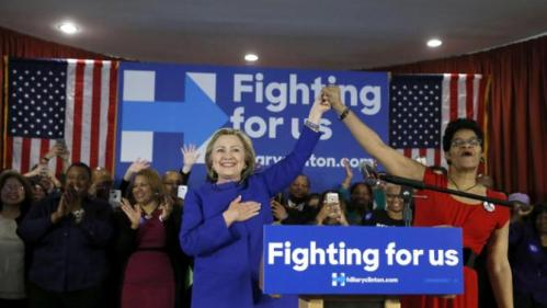 Democratic presidential candidate Hillary Clinton, left, responds to the crowd's applause after an introductory poem by Geneva Reed-Veal, the mother of Sandra Bland, who was found dead in a Texas jail cell, Wednesday, Feb. 17, 2016, during a campaign stop in Chicago. (AP Photo/Charles Rex Arbogast)
