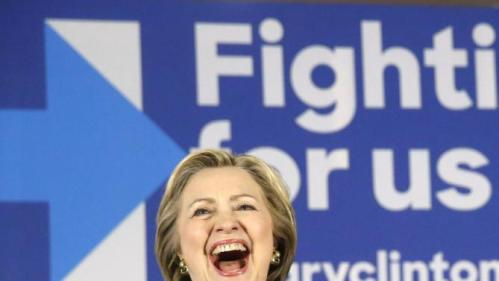 Democratic presidential candidate Hillary Clinton, laughs during an introductory poem by Geneva Reed-Veal, the mother of Sandra Bland, who was found dead in a Texas jail cell, Wednesday, Feb. 17, 2016, during a campaign stop in Chicago. (AP Photo/Charles Rex Arbogast)