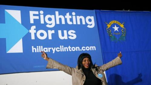A woman poses for a photo in front of a sign after a rally with Democratic presidential candidate Hillary Clinton, Thursday, Feb. 18, 2016, in Las Vegas. (AP Photo/John Locher)